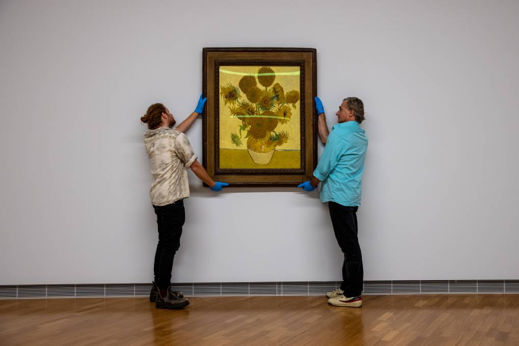 Joel Arthur and Lloyd Hurrell of the National Gallery hang Vincent Van Gogh's famous Sunflowers in the lead-up to the opening of Botticelli to Van Gogh, the gallery's next blockbuster. Picture: Keegan Carroll