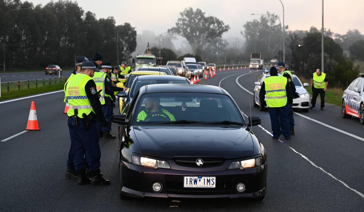 PERMIT CHECK: NSW Police were looking at permits in all cars crossing the border from Victoria into NSW on Wednesday. Picture: MARK JESSER